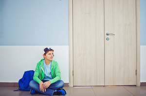 Cute Schoolboy With Backpack Sitting On The Floor By Classroom Door