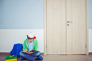 Cute Schoolboy Writing Notes In Exercise-book While Sitting On The Floor By Classroom Door