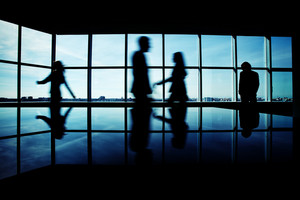 Silhouettes Of Several Office Workers Walking On Background Of Window