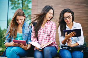 Company Of Attractive Teenage Girls Reading Outside
