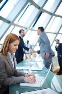 漂亮的女實業家網絡或規劃工作在後台的同事握手