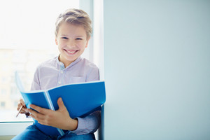 Portrait Of Smiling Schoolboy With Exercise-book Looking At Camera