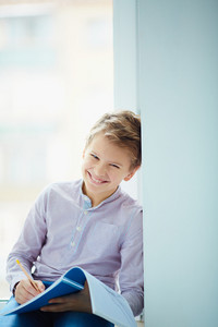 Portrait Of Smiling Schoolboy Making Notes In Exercise-book And Looking At Camera