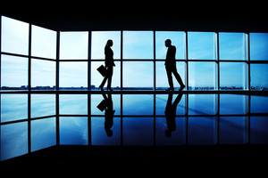 Outlines Of Two Business Partners Standing By The Window