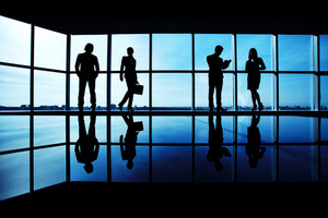 Silhouettes Of Several Office Workers Standing On Background Of Window