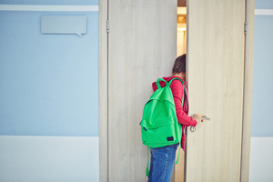 Pre-teen Schoolboy Late For Lesson Looking Into Classroom