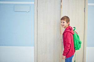 Happy Schoolboy With Backpack Opening Classroom Door
