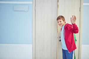 Happy Schoolboy With Backpack Opening Classroom Door And Waving His Hand