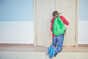 Pre-teen Schoolboy With Backpack Peeping Into Keyhole Of Classroom Door