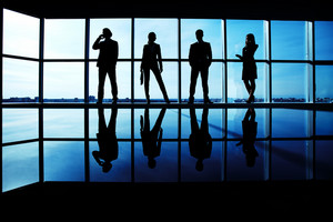 Silhouettes Of Several Office Workers Standing By The Window In Line
