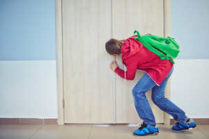 Curious Learner With Backpack Peeping Into Keyhole Of Classroom Door