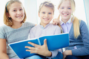 Portrait Of Three Happy Classmates With Exercise Book Looking At Camera And Smiling