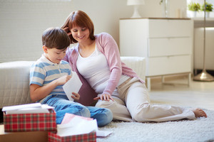 Portrait Of Cute Boy Opening Envelope With His Mother Near By At Home