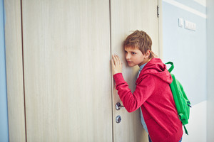 Curious Youngster With Backpack Eavesdropping By Classroom Door