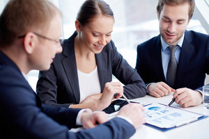 Confident Business People Discussing Financial Document At Meeting