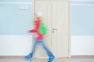 Schoolboy With Backpack Going Fast By Classroom Door