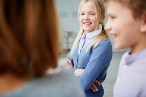 Portrait Of Happy Schoolgirl Looking At Camera With Her Classmates Near By