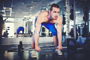 Portrait Of Sporty Topless Man Weightlifting In Gym