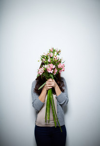 Portrait Of Young Female Hiding Her Face Behind Bunch Of Fresh Flowers In Isolation