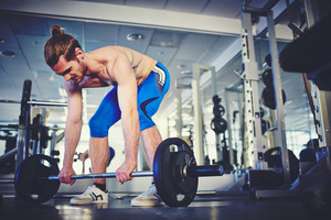 Portrait Of Strong Sportsman Weightlifting In Gym
