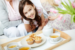 Teacups And Cupcakes On Tray And Cute Little Girl Looking At Camera Near By With Her Mother And Grandmother On Background
