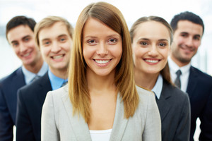 Happy Businesswoman Looking At Camera With Smart Associates Behind
