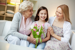 Portrait Of Happy Little Girl Holding Bunch Of Pink Tulips With Her Mother And Grandmother Looking At Her
