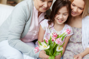 Bunch Of Tulips Held By Senior Woman With Her Daughter And Granddaughter Near By