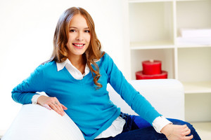 Portrait Of Young Female Sitting On Sofa And Looking At Camera