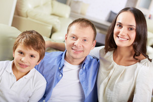 Portrait Of Happy Family Of Three Looking At Camera