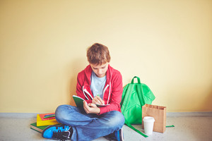 Cute Schoolboy Making Notes In Exercise-book While Sitting On The Floor By Wall
