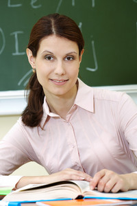 Portrait Of Smart Teacher At Workplace Looking At Camera