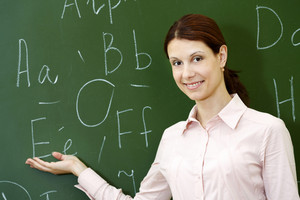 Portrait Of Smart Teacher Pointing At Letters On Blackboard And Looking At Camera