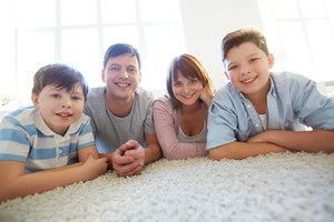 Portrait Of Happy Family Of Four Looking At Camera With Smiles