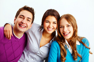 Portrait Of Three Joyful Friends Looking At Camera On White Background