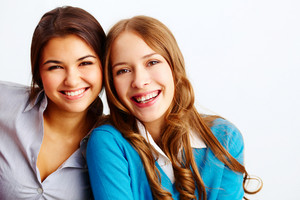 Portrait Of Joyful Girls Looking At Camera On White Background