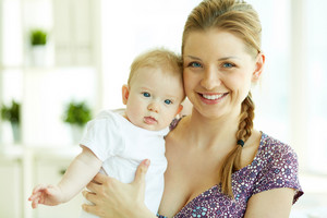 Portrait Of Happy Young Mother Holding Her Little Daughter And Looking At Camera With Smile