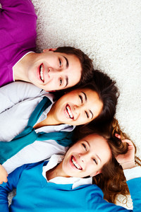 Above Angle Of Three Laughing Friends Looking At Camera