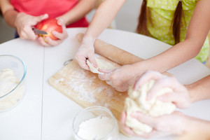 Hands Of Little Girl Helping Her Mother And Sister Cook Pastry