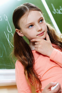 Photo Of Pensive Girl By The Blackboard Touching Her Chin While Thinking Of Difficult Formula