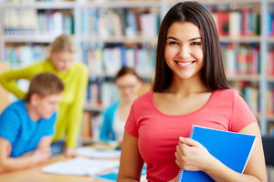 Portrait Of Pretty Girl Looking At Camera In College Library With Her Group Mates On Background