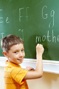 Portrait Of Smart Schoolchild By The Blackboard Looking At Camera