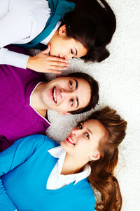 Above Angle Of Teenage Girl Whispering To Guy Ear With Their Friend Near By