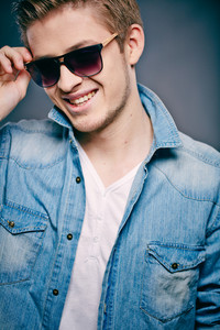 A Young Guy In Sunglasses Posing In Front Of Camera