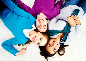 Above Angle Of Attractive Friends Looking At Camera While Lying On The Floor