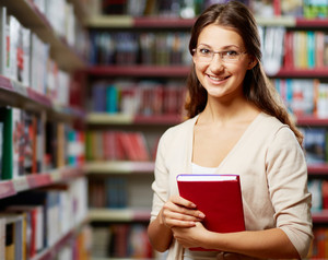 Portrait Of Clever Student With Book In College Library