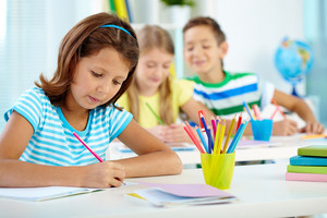 Portrait Of Serious Girl Drawing At Workplace With Her Schoolmates On Background