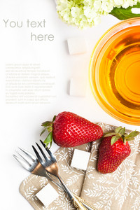 Cup Of Tea And Strawberries Over White