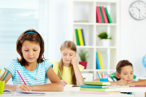 Portrait Of Cute Girl Drawing At Workplace With Her Schoolmates On Background