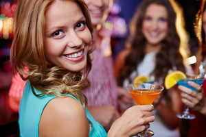 Portrait Of Cheerful Girl Holding Cocktail In Martini Glass And Looking At Camera On Background Of Her Friends At Party